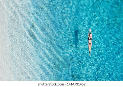 Aerial view of a girl on ocean on Bali, Indonesia. Vacation and adventure. Turquoise water. Top view from drone at ocean, azure watre and relax girl. Travel and relax - image