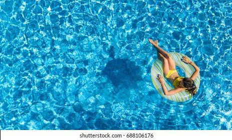 Vista aérea de una chica en la piscina desde arriba, un niño nade en un anillo inflable y se divierte en el agua en vacaciones familiares