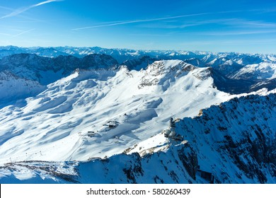 Aerial view of the glaciers on top of Germany's tallest mountain, the Zugspitze, with the Zugspitz skiing resort on a beautiful cloudless winter morning.