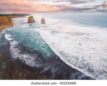 Aerial view of the Gog and Magog rock formations at sunset with breaking ocean waves