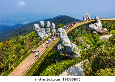 Aerial view of the Golden Bridge is lifted by two giant hands in the tourist resort on Ba Na Hill in Da Nang, Vietnam. Ba Na mountain resort is a favorite destination for tourists - Shutterstock ID 1343264873
