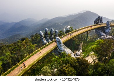 Aerial view of the Golden Bridge is lifted by two giant hands in the tourist resort on Ba Na Hill in Danang, Vietnam. Ba Na mountain resort is a favorite destination for tourists - Shutterstock ID 1343264876