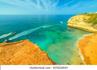 Aerial view of golden cliffs of Praia de Benagil in Algarve near Lagoa, Portugal, Europe. Boat trips to visit the famous landmark Algar de Benagil, the cave near Benagil Beach. Tourism in Algarve.