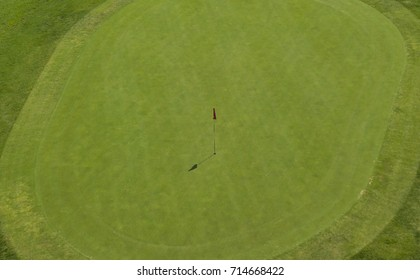 Aerial view of a golf course. In detail you can see the lawn of the final hole and the red flag of signaling. The sun shines and is an ideal day for sports and outdoor activities.