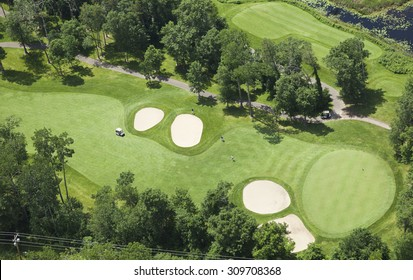 Aerial view of a golf course fairway and green with sand traps, trees and golfers
