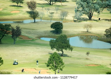 An aerial view of a golf course, with golfers around a sand pit.