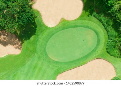 Aerial view of golf course with green fairway and bunker