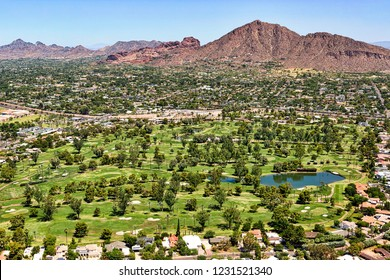 Aerial view of a golf course and homes below Camelback Mountain in Phoenix, Arizona