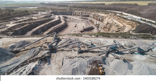 Aerial view of the granite quarry. Development of granite rock in Ukraine. Processing plant for crushed stone and gravel. Mining and Quarry mining equipment.