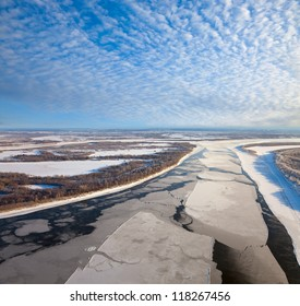 Aerial view of the great river with floating ice floes during the spring day. Drifting of ice. Driving of ice. Ice floe.
