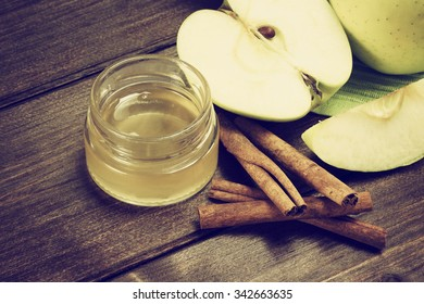 Aerial view of a green apples sliced, a jar of honey and a cinnamon lying on a wooden table. Photo is edited as a vintage with dark edges.