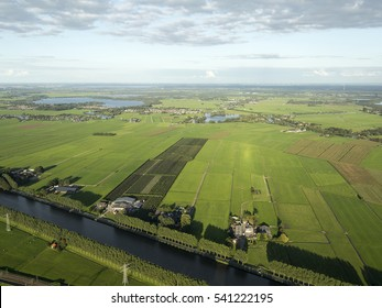 Aerial view of green fields with some farm houses at the canal Amsterdam-Rijnkanaal in The Netherlands. There is a beautiful sky with high clouds and a crystal clear horizon.