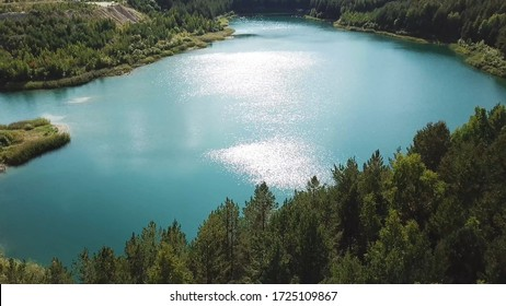 Aerial view of green forest and lake shore. Flying over breathtaking summer natural landscape with turquoise lake surrounded by pine tree forest.