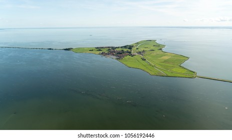 Aerial view of a green island in a huge lake with a crystal clear horizon and blue sky. It is the peninsula Marken in the Markermeer, Holland.