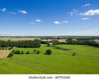 Aerial view of a green meadow with blue sky over germany