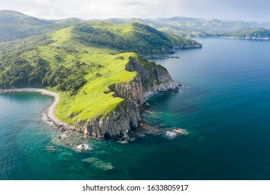 Aerial view of green rocky coastline and clean turquoise sea in Asia.  Cape Azaryev at Gamov Peninsula in summertime. Seaside nature landscape in Primorsky Krai, Far East, Russia