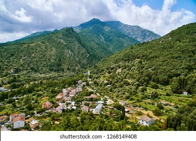 Aerial view of green surroundings of Corte town in Corsica with mountains in background