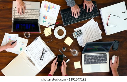 aerial view of a group of business people analyzes financial options on a brown office desk