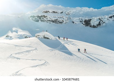 Aerial View of Group of touring skiers. Ski touring in the mountains. From Above. Ski tour group. Free ride in Romania. Winter sunny day. Winter sport. Group of alpine touring skiers