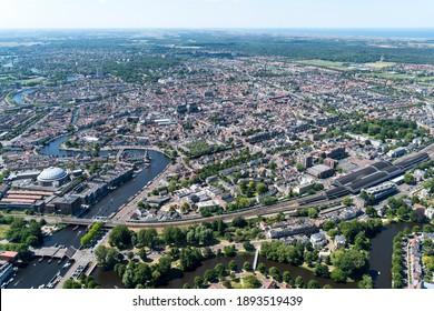 Aerial view of Haarlem and the downtown area in Holland. Left jail Koepelgevangenis and river Spaarne with historic dutch houses at the waterfront. Right Central Station and sea Noordzee at horizon.