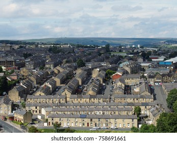 aerial view of halifax in west yorkshire shwoing residential streets and terraced houses with hills in the background
