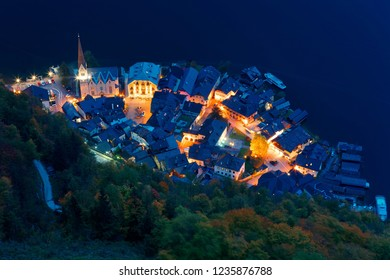 Aerial view of Hallstatt at dusk, an amazing lakeside village by the mountainside in Salzkammergut region of Austria, in colorful autumn season ~ Aerial night view of Beautiful lakeside harbor (port)