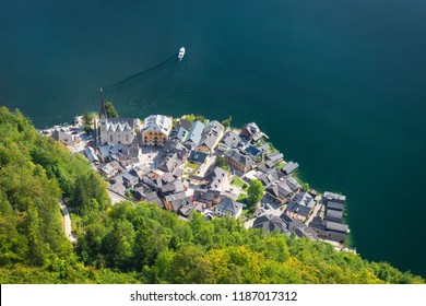Aerial view of Hallstatt village and blue water in Hallstatter lake, Austria Europe, with view of forest house with tourist travel in village and dirt road for hiking, trail, and transportation