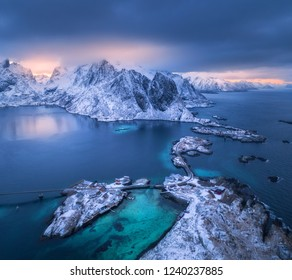 Aerial view of Hamnoy at dramatic sunset in winter in Lofoten islands, Norway. Moody landscape with blue sea, snowy mountains, rocks, village, buildings, rorbuer, road, bridge, cloudy sky. Top view