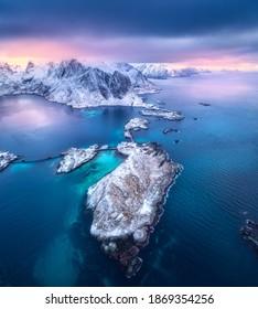 Luftbild von Hamnoy bei dramatischem Sonnenuntergang im Winter auf den Lofoten Inseln, Norwegen. Landschaft mit blauem Meer, schneebedeckten Bergen, Felsen und Inseln, Dorf, Gebäude, Straße, Brücke, bewölkter rosa Himmel. Draufsicht