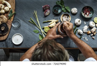Aerial view of hands crushing asian ingredients with mortar and pestle