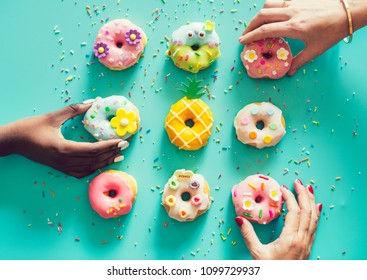 Aerial view of hands picking donuts