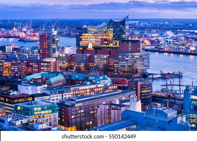 """Aerial view of the harbor district, the concert hall """"Elbphilharmonie"""" and downtown Hamburg, Germany, at dusk."""