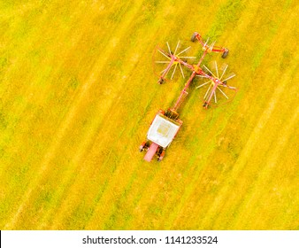 Aerial view to harvester on meadows. Harvest of hay field. Industrial background on agricultural theme. Agricultural production from above. Agriculture and environment in European Union.