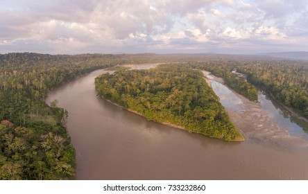 Aerial view of a heart shaped island in Rio Napo, the Ecuadorian Amazon at dawn. The early morning sunlight is illuminating the treetops.