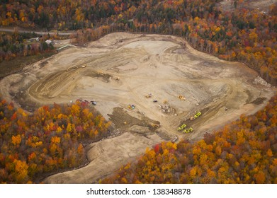 Aerial view of heavy equipment excavating site surrounded by fall foliage, Stowe, Vermont, USA