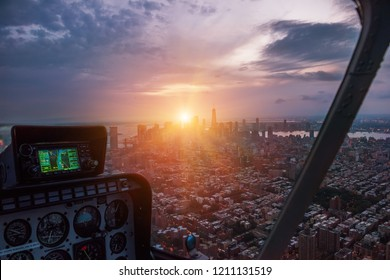 Aerial view from the helicopter cabin on the evening city of New York. The last rays of the setting sun illuminate the city.