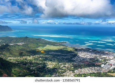 Aerial view of helicopter from high a ridge trail overlooking Kaneohe on Oahu, Hawaii