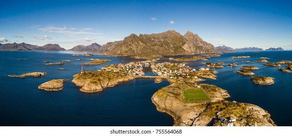 Aerial view of Henningsvaer, its scenic football field and mountains in the background. Henningsvaer is a fishing village located on several small islands in the Lofoten archipelago in Norway