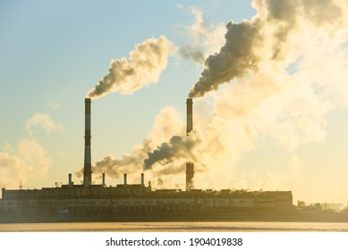Aerial view of high chimney pipes with grey smoke from power plant. Production of electricity with fossil fuel. Factory polluting air. Global warming concept