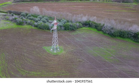 Aerial view of a high red and white metal tower that acts as a radio antenna and support for high voltage cables. It is located in the countryside, with trees and fields. There is nobody.