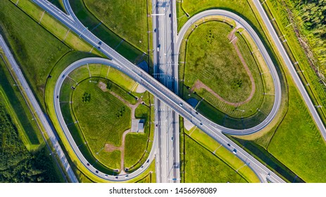 Aerial view of highway in city. Cars crossing interchange overpass. Highway interchange with traffic. Aerial bird's eye photo of highway. Expressway. Road junctions. Car passing. Top view from above.