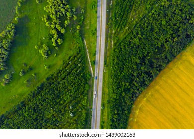 aerial view of highway going through the green and yellow summer fields