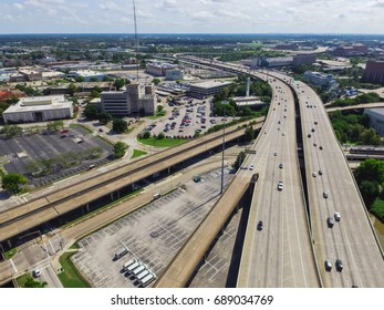 Aerial view highway I45 (Gulf Freeway), asphalt elevated road and Bayou River in downtown Houston, Texas, US. Passenger cars, trucks commuting daytime. Parking garage and office building in background