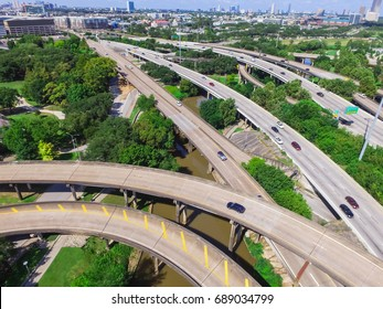 Aerial view highway I45 (Gulf Freeway), asphalt elevated road and Bayou River in downtown Houston, Texas, US. Passenger cars and trucks commuting daytime. Midtown office buildings are in the distance.