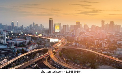 Aerial view highway interchange in city downtown sunset tone, cityscape background