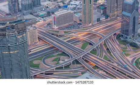 Aerial view of highway interchange in Dubai downtown night to day transition timelapse from viewpoint. Cityscapes traffic bridge, logistics. Roads and lanes Crossroads, Dubai, United Arab Emirates