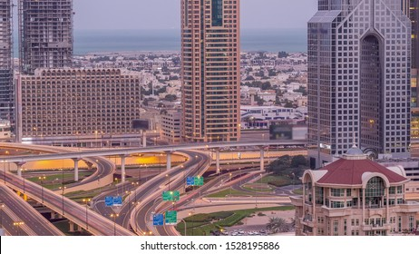 Aerial view of highway interchange in Dubai downtown night to day transition timelapse. Cityscapes traffic bridge, logistics. Roads and lanes Crossroads, Dubai, United Arab Emirates
