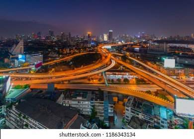Aerial view of highway interchange junction in Bangkok city downtown at sunset with cityscape background, Bangkok, Thailand.