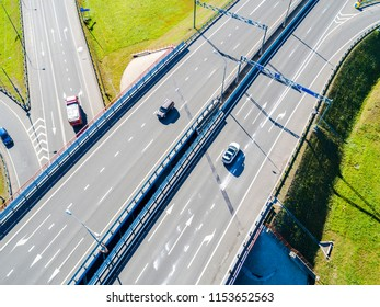 Aerial view of highway and overpass in city. Aerial view of cars crossing interchange overpass. Highway interchange with traffic. Aerial bird's eye photo of highway passing. Expressway. Road junctions