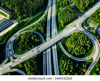 Aerial view of highway and overpass with green woods on a summer day in Finland.